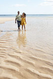 Young Couple Walking Along Shoreline Holding H Stock Images