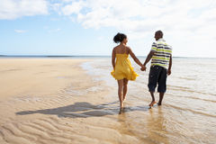 Young Couple Walking Along Shoreline Holding H. Romantic Young Couple Walking Along Shoreline Of Beach Holding Hands Royalty Free Stock Photography