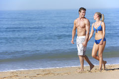 Young Couple Walking Along Summer Beach Royalty Free Stock Images