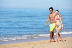 Young Couple Walking Along Summer Beach Stock Images