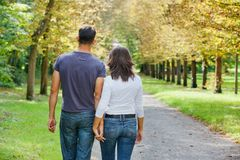 Young Couple Walking in autumn park. Romentic Beautiful young couple walking in autumn park royalty free stock images