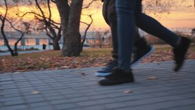 A young couple is walking in the autumn park against the backdrop of a beautiful sunset. Legs of two romantic people