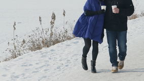 Young couple walking on bank of frozen river in snowy winter outdoors. Young couple walking in snowy winter outdoors. Happy female in blue coat, long black stock footage