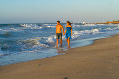 Young couple walking barefoot on a wet beach at dusk. Stock Photo