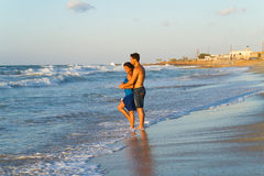 Young couple walking barefoot on a wet beach at dusk. Royalty Free Stock Image