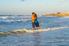 Young couple walking barefoot on a wet beach at Stock Images
