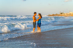 Young couple walking barefoot on a wet beach at Stock Photo