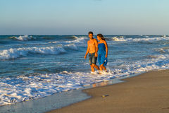 Young couple walking barefoot on a wet beach at Royalty Free Stock Photography