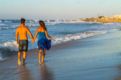 Young couple walking barefoot on a wet beach at Stock Photos