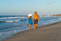 Young couple walking barefoot on a wet beach at Stock Photography