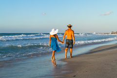 Young couple walking barefoot on a wet beach at Royalty Free Stock Photo