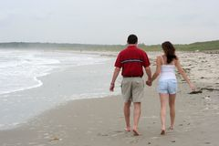 Young couple walking on beach. Holding hands Stock Images