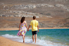 Young couple walking on the beach. Young couple holding hands and walking carefree on the beach on summer vacation stock image