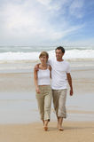 Young couple walking on the beach. Young man and woman walking along the beach Royalty Free Stock Images