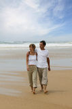 Young couple walking on the beach. Young man and woman walking along the beach looking at the view Stock Image