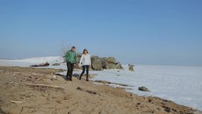Young couple walking on the beach with the dog. spring beach with snow stock footage