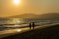 Young couple walking at the beach stock photography