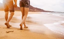 Young couple walking on the beach. Young couple in love walking on the beach at the sunset with copy space stock photos
