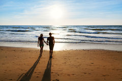 Young couple walking on the beach Stock Photos