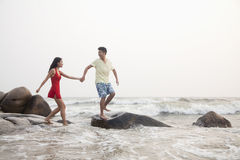 Young couple walking on the beach walking over rocks holding hands Stock Images