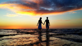 Young couple walking on the beach in the waves Royalty Free Stock Photos
