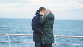 Young couple walking on a beach in winter or autumn at cold day stock footage