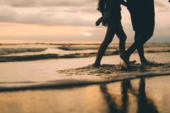 A couple walking near the ocean watching sunset royalty free stock image