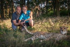 Young couple walking with cheetah Royalty Free Stock Photo