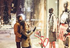 Young couple walking in the city center and window-shopping at night. Valentine`s day sales royalty free stock image