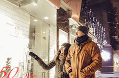 Young couple walking in the city center and window-shopping at night. Royalty Free Stock Photo