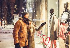Young couple walking in the city center and window-shopping at night. Royalty Free Stock Photos