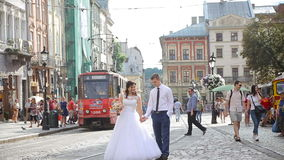 Young couple walking in city near tram stock footage