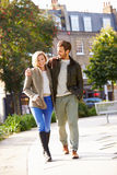 Young Couple Walking Through City Park Together Stock Photo