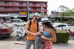 Young Couple Walking City Street Cheerful Man And Woman Tourists With Backpacks Exploring Asian Town Together. During Vacation Royalty Free Stock Photo