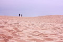 Young couple walking in the desert. Dune du Pilat, France. Young couple walking down the sand beach Dune du Pilat in France. Biggest Dune in the Europe royalty free stock photography