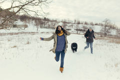 Young couple walking with a dog in a winter day Royalty Free Stock Photo