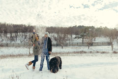 Young couple walking with a dog in a winter day Royalty Free Stock Photos