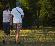 Young Couple Walking Down The Meadow. Young casual dressed couple walking down the meadow in summer clothes Royalty Free Stock Image