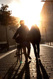 Young couple walking down the street with a bicycle at sunset. Royalty Free Stock Photos
