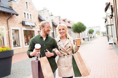 Young couple walking and drinking coffee with shopping bags on the street Royalty Free Stock Image