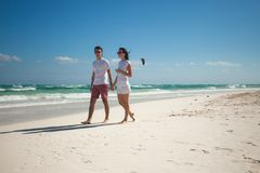 Young couple walking on exotic beach in sunny day Royalty Free Stock Photos