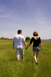 Young Couple Walking in Field Royalty Free Stock Photo