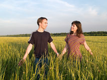 Young Couple Walking Field Holding Hands. Looking each other Stock Image