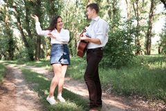 Young couple walking in the forest, playing guitar and dancing, summer nature, bright sunlight, shadows and green leaves, romantic royalty free stock photo