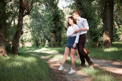 Young couple walking in the forest, playing guitar and dancing, summer nature, bright sunlight, shadows and green leaves, romantic stock photo