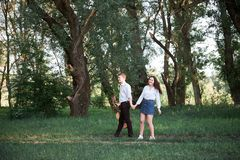 Young couple walking in the forest and playing guitar, summer nature, bright sunlight, shadows and green leaves, romantic feelings stock photo