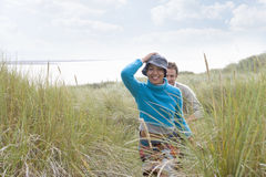 Young couple walking through grass at beach royalty free stock images