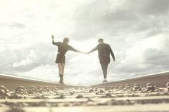 Young couple walking hand in abandoned rails in a surreal place. Young couple in love walking hand in abandoned rails in a surreal place Stock Image