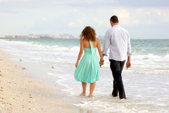 Young couple walking hand in hand on the beach thi. A young couple walking hand in hand along the beach, their feet ate in the water, they have their backs to Stock Photos