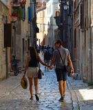 Young couple walking hand in hand through the streets of the old town Rovinj  Istria Croatia. ROVINJ, ISTRIA, CROATIA - JUNE 18, 2017: Young couple walking hand Stock Photos